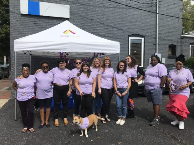 Group of 11 people and two dogs wearing purple EmPower Challenge t-shirts in front an Action Alliance tent.