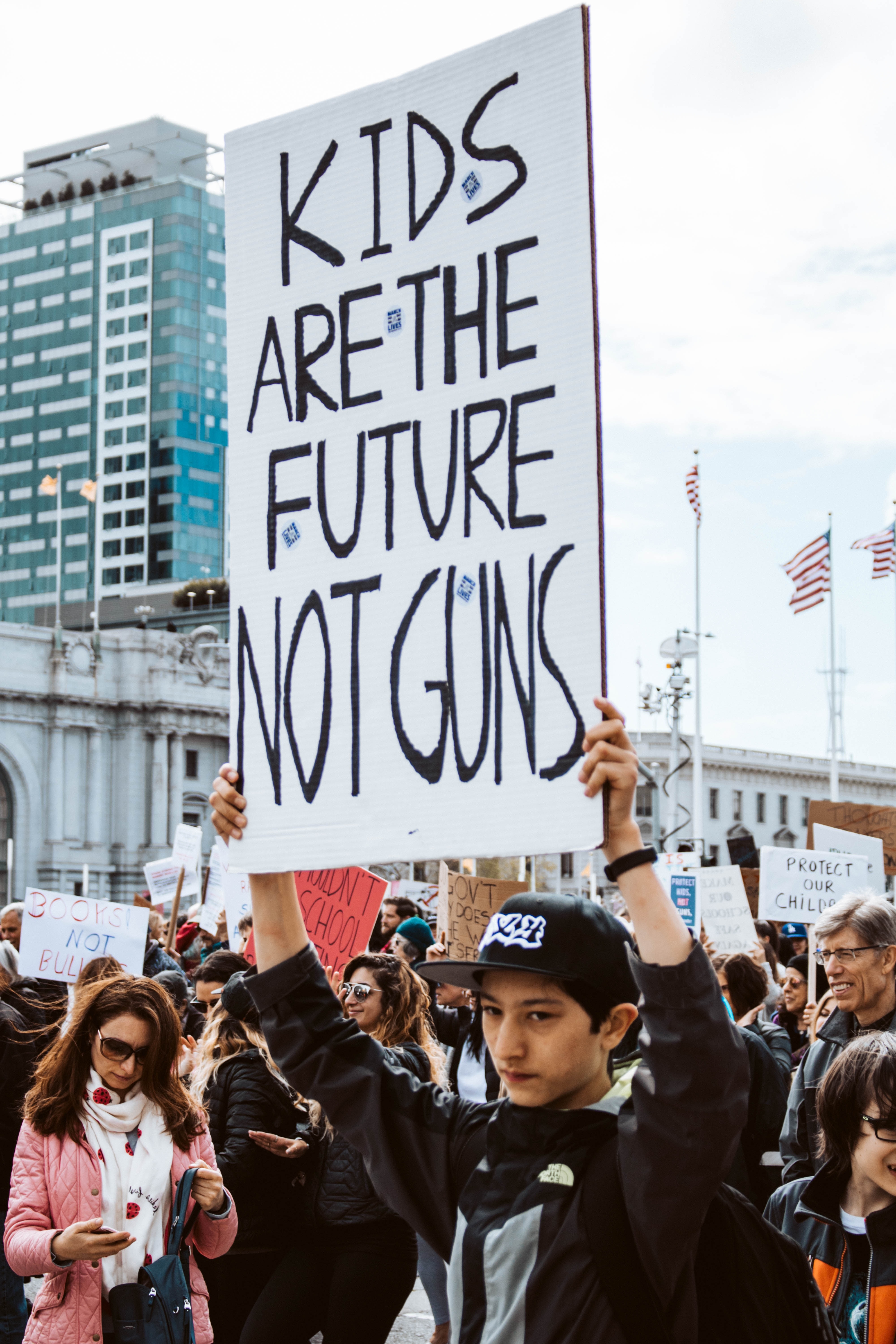 "Several people at a rally in front of a building with one young person in the foreground holding a sign that reads, ""Kids are the Future Not Guns"""