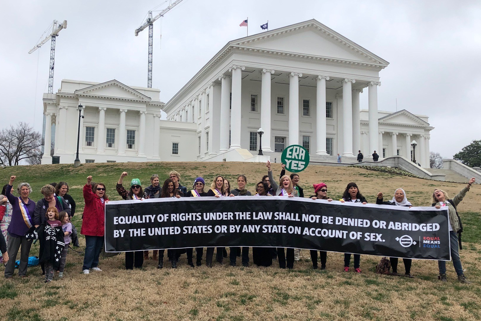 """Group of a couple dozen people with arms raised in victory behind a long banner that reads, """"Equality of Rights Under the Law Shall Not Be Denied or Abridged by the United States or by Any State on Account of Sex"""" standing in front of the Virginia State Capitol."""