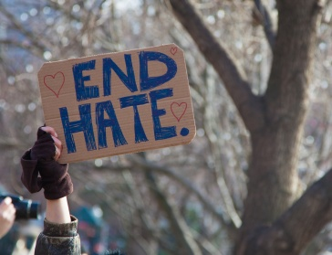 "Hand holding sign saying ""End Hate"""