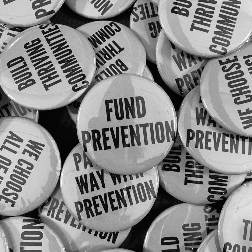 "A grayscale photo of a collection of medium-sized buttons with different phrases, including ""build thriving communities,"" ""we choose all of us,"" ""pave the way with prevention,"" and the central focus is on a button with the words, ""Fund Prevention."""